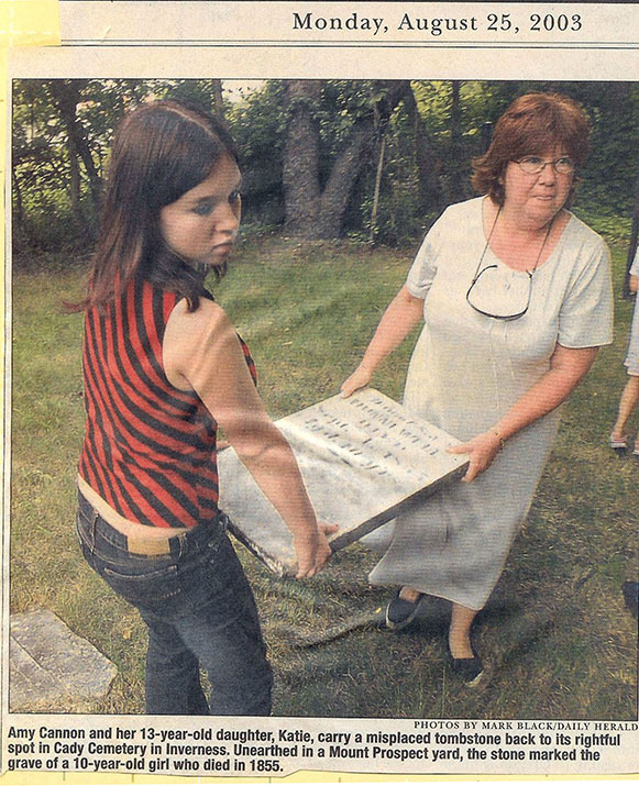 Amy Cannon and her 13-year-old daughter, Katie, carry a misplaced tombstone back to its rightful spot in Cady Cemetery in Inverness. Unearthed in a Mount Prospect yard, the stone marked the grave of a 10-yr-old girl who died in 1855.